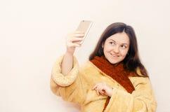 Het jonge donkerbruine meisje in een badjas maakt selfie royalty-vrije stock afbeeldingen
