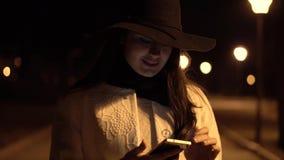 Het jonge donkerbruine meisje in een hoed loopt bij nachtpark en begint om haar telefoon te controleren stock video