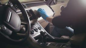 Het jonge donkerbruine meisje in handschoenen wast met borstel een een autodashboard en stuurwiel royalty-vrije stock foto
