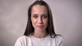 Het jonge donkerbruine meisje let op bij camera, het glimlachen, grijze achtergrond stock videobeelden