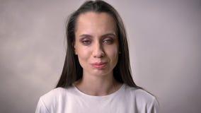 Het jonge donkerbruine meisje let op bij camera, het glimlachen, vreugdeconcept, grijze achtergrond stock footage
