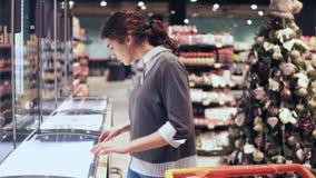Het jonge donkerbruine meisje neemt een pak van boter van de diepvriezer Het winkelen bij lokale kruidenierswinkelopslag stock footage