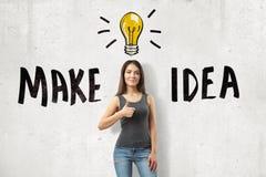 Het jonge donkerbruine meisje toevallige jeans dragen en de t-shirt die duim tonen met MAKEN omhoog IDEE tot teken en beeldverhaa stock fotografie