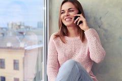 Het jonge donkerbruine spreken op smartphone terwijl het zitten op wi Royalty-vrije Stock Fotografie