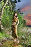 Het jonge donkerbruine vrouw stellen in groene wildernis stock fotografie