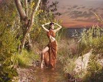 Het jonge donkerbruine vrouw stellen in groene wildernis royalty-vrije stock foto