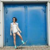 Het jonge donkerbruine vrouw stellen met skateboard stock fotografie