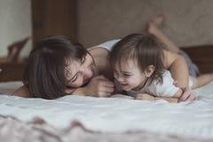 Het jonge donkere haired moeder en dochterpeuter spelen, geknuffel Stock Afbeelding