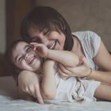 Het jonge donkere haired moeder en dochterpeuter spelen, geknuffel Royalty-vrije Stock Foto's