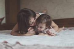 Het jonge donkere haired moeder en dochterpeuter spelen, geknuffel Royalty-vrije Stock Fotografie
