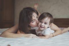 Het jonge donkere haired moeder en dochterpeuter spelen, geknuffel Stock Fotografie