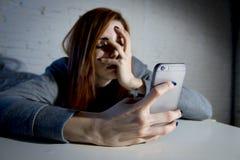 Het jonge droevige kwetsbare meisje die mobiele telefoon met behulp van deed schrikken en het wanhopige lijdende online misbruik  Stock Foto