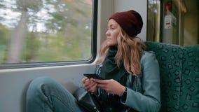 Het jonge eenzame Kaukasische verstoorde meisje in een rood GLB berijdt een metro of tramtrein, gebruikt een smartphone, en kijkt stock video