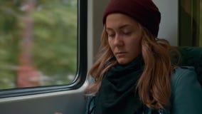 Het jonge eenzame Kaukasische verstoorde meisje in rode GLB-ritten in een metro of tramtreinauto, gebruikt de telefoon, drukt een stock video