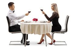 Het jonge elegante paar roosteren met wijn bij een lijst stock foto's