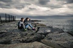 Het jonge en aantrekkelijke die paar zit op de pijler van stenen wordt gemaakt Royalty-vrije Stock Foto