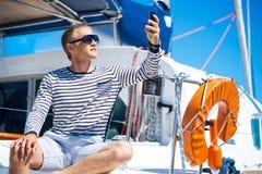 Het jonge en knappe mens ontspannen op een varende boot Royalty-vrije Stock Foto's
