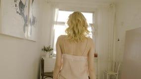 Het jonge en mooie blondevrouw stellen dichtbij het venster actie Daglicht van het venster Sexy blonde in de zonruimte stock videobeelden