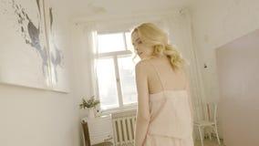 Het jonge en mooie blondevrouw stellen dichtbij het venster actie Daglicht van het venster Sexy blonde in de zonruimte stock video