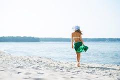 Het jonge en sexy vrouw stellen in een hoed op het strand royalty-vrije stock afbeeldingen