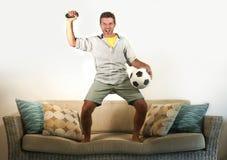 Het jonge enthousiaste voetbalventilator het vieren doel gekke gelukkige springen op banklaag die thuis voetbal op spel op televi stock foto