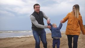 Het jonge familie genieten die op het strand lopen Man, vrouwenmeisje en jongen stock footage
