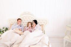 Het jonge familie geworden zieke of zieke thuis niezen in bed Stock Foto's
