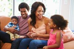 Het jonge Familie Ontspannen op Sofa Together Stock Fotografie