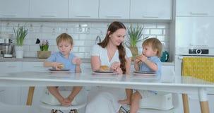 Het jonge familiemamma en twee zonen die in de keuken bij het wit zitten dienen samen het eten van burgers en het hebben van pret stock videobeelden