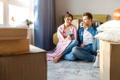 Het jonge familiepaar kocht of huurde hun eerste flatje Zij zitten in vloer en drank van blauwe koppen chilling stock foto's