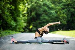 Het jonge flexibele meisje, die op de streng zitten, rekte zich vóór trai uit royalty-vrije stock afbeelding