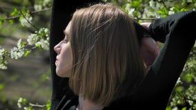 Het jonge geïnspireerde meisje rekt zich in park in dag in de zomer uit, lettend op bij camera, bloeiboom op achtergrond stock footage