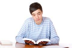 Het jonge geconcentreerde mannelijke boek van de studentenlezing royalty-vrije stock foto's