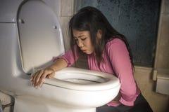 Het jonge gedronken of zwangere Aziatische vrouw braken en het werpen omhoog in toiletwc die onwel en zieke lijdende maag voelen  royalty-vrije stock foto
