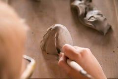 Het jonge geitje beeldhouwt van klei Het proces van spijkers stock foto