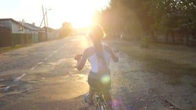 Het jonge geitje berijdt onderaan straat op fiets Langzame Motie stock video