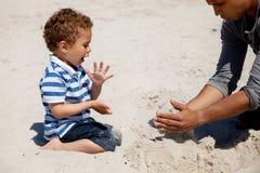 Het jonge geitje dat als Zijn Papa kijkt maakt Zandkasteel Royalty-vrije Stock Foto