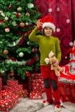 Het jonge geitje die van Cherfulkerstmis snuisterij tonen royalty-vrije stock foto