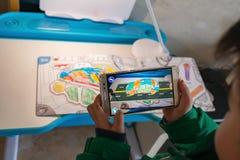Het jonge geitje die Vergrote Werkelijkheids popup schilderijen van een kleur spelen vulde auto en weg via mobiel Stock Fotografie