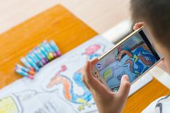Het jonge geitje die Vergrote Werkelijkheids popup schilderijen van een kleur spelen vulde draak via mobiel Stock Afbeelding