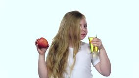 Het jonge geitje drinkt sap van een glas en houdt een appel Witte achtergrond Langzame Motie stock footage