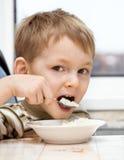 Het jonge geitje eet havermoutpap Stock Foto