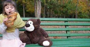 Het jonge geitje eet zoet broodje in openlucht met papaver op bank met teddybeerstuk speelgoed bij speelplaats in de herfstpark stock video