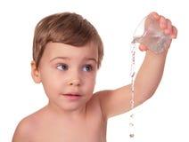 Het jonge geitje giet water van glas uit Royalty-vrije Stock Afbeeldingen