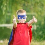 Het jonge geitje in het super heldenkostuum tonen beduimelt omhoog stock foto