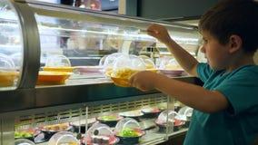 Het jonge geitje in koffie kijkt op showcase met smakelijk voedsel bij het bewegen van platen en neemt spaghetti stock video