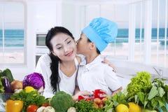 Het jonge geitje kust zijn moeder terwijl het koken Stock Foto