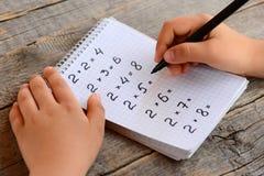 Het jonge geitje lost vermenigvuldigingsvoorbeelden op Het jonge geitje houdt een teller in zijn hand en schrijft antwoorden aan  Stock Foto