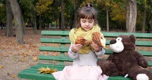 Het jonge geitje met twee stukken van broodje met papaver in handen zit dichtbij teddybeer op bank bij speelplaats in de herfstpa stock videobeelden