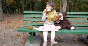 Het jonge geitje met twee stukken van zoet broodje in handen zit op bank met stuk speelgoed bij speelplaats in de herfstpark stock video